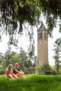 Two people sitting on the lawn in front of the campanile.